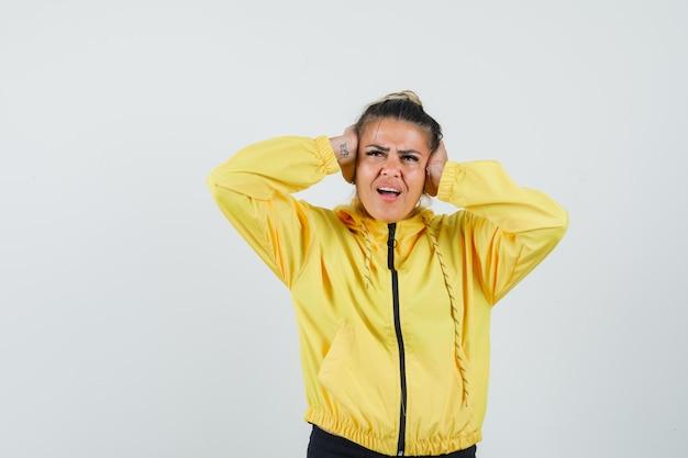 Женщина в спортивном костюме закрывает уши руками и выглядит раздраженной, вид спереди.