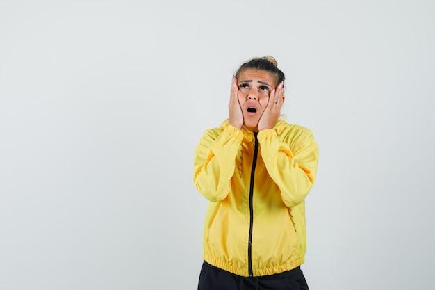 Женщина в спортивном костюме, взявшись за руки на щеках и глядя задумчиво, вид спереди.