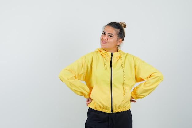 Женщина в спортивном костюме, взявшись за руки на талии и выглядя уверенно, вид спереди.