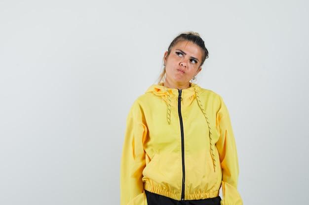 Женщина в спортивном костюме смотрит вверх и задумчиво, вид спереди.