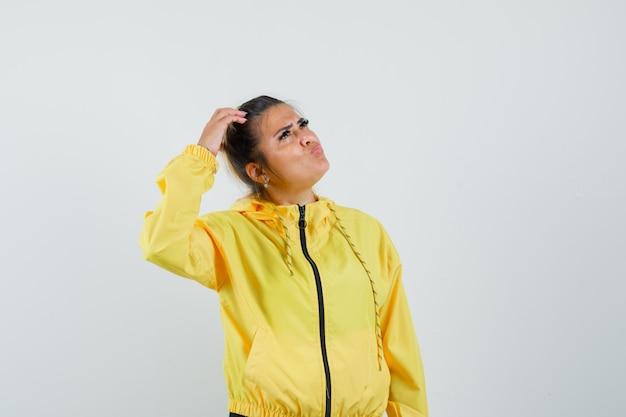 Женщина в спортивном костюме почесывает голову и смотрит задумчиво, вид спереди.
