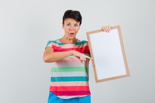 縞模様のtシャツの女性、空のフレームを指して驚いたように見えるパンツ、正面図。