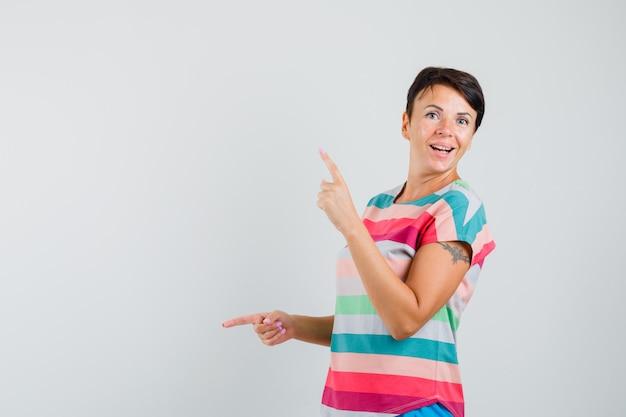 指を上下に指して幸せそうに見えるストライプのtシャツの女性、正面図。