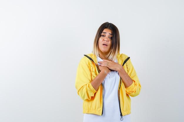 여성 t- 셔츠, 재킷 가슴에 손을 유지 하 고 의아해, 전면보기를 찾고.