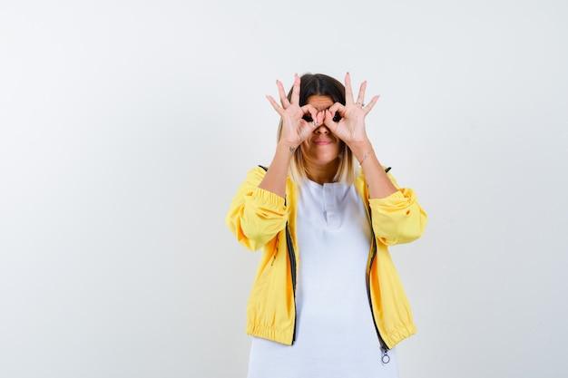 Tシャツを着た女性、メガネのジェスチャーを示し、焦点を合わせて見えるジャケット、正面図。
