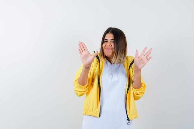 Tシャツを着た女性、降伏のジェスチャーで手のひらを示し、自信を持って見えるジャケット、正面図。