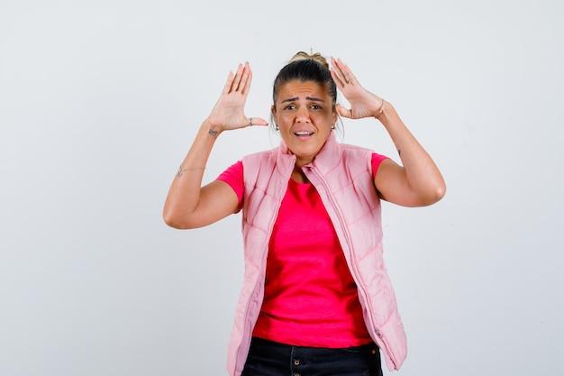 Tシャツを着た女性、頭の近くで挙手を保ち、困惑しているように見えるベスト