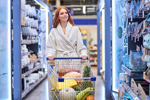 Женщина в отделе посуды, выбирает тарелки и сковороды для дома, одна, в халате. в супермаркете