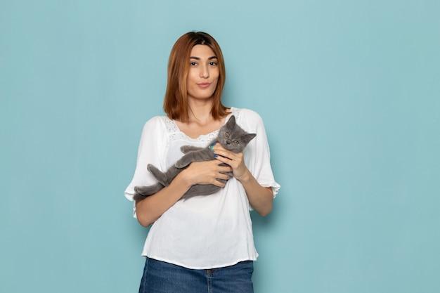 白いブラウスと灰色の子猫を保持しているブルージーンズの女性