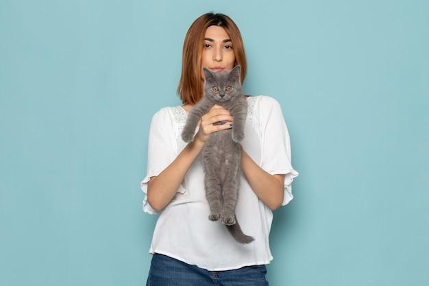 Женщина в белой блузке и синих джинсах держит маленького симпатичного серого котенка