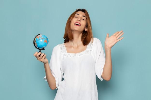 Женщина в белой блузке и синих джинсах держит глобус