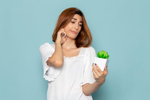 白いブラウスと小さな緑の植物を保持しているブルージーンズの女性