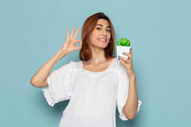 Женщина в белой блузке и синих джинсах держит маленькое растение и улыбается