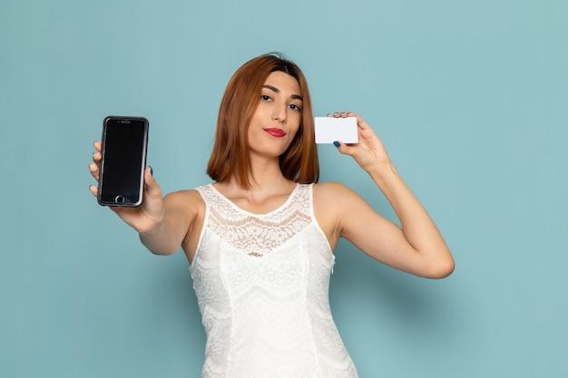 電話とカードを保持している白いブラウスとブルージーンズの女性