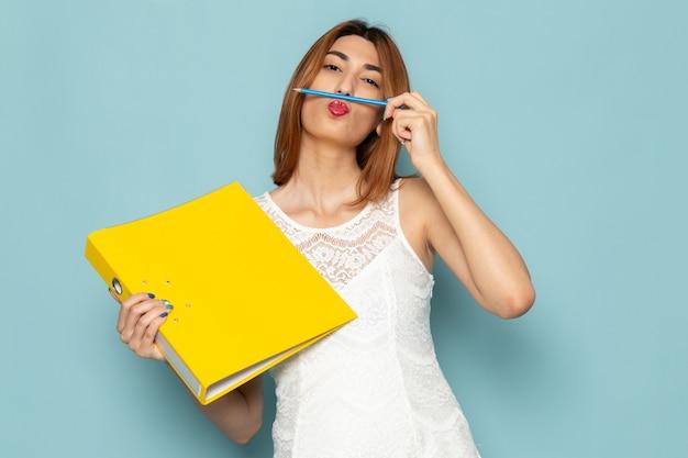 白いブラウスと黄色のファイルとペンを保持しているブルージーンズの女性