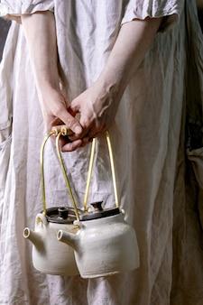 伝統的な日本の茶道のための2つの白い手作りのセラミックティーポットを保持している白い綿のドレスの女性。ティードリンク