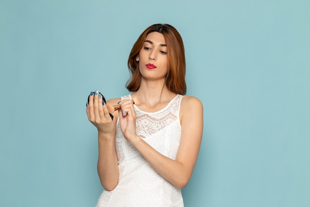 メイクをしている白いドレスの女性