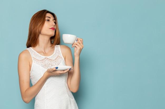 お茶を飲む白いドレスの女性