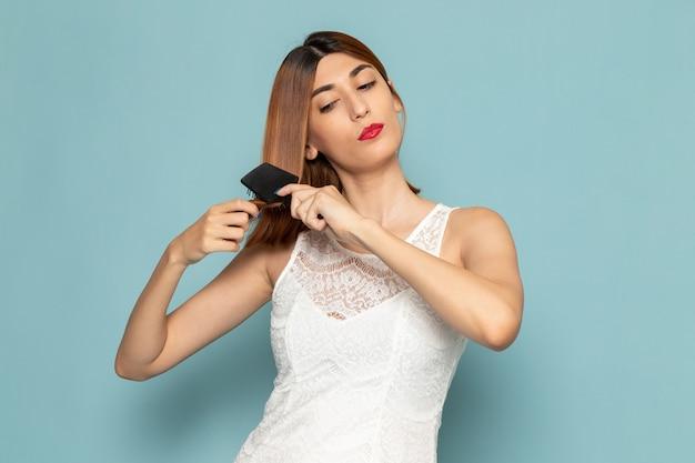 Женщина в белом платье поправляет волосы