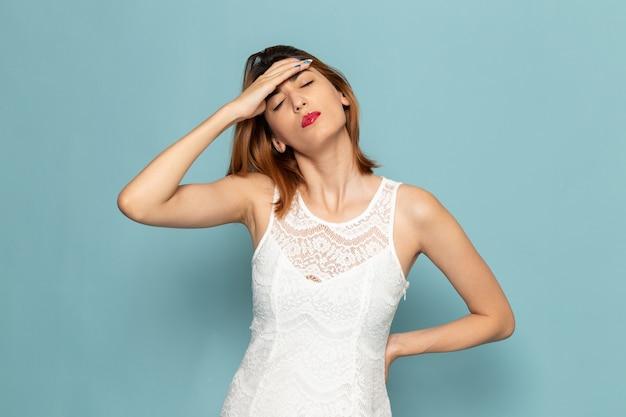 頭痛を持つ白いドレスの女性
