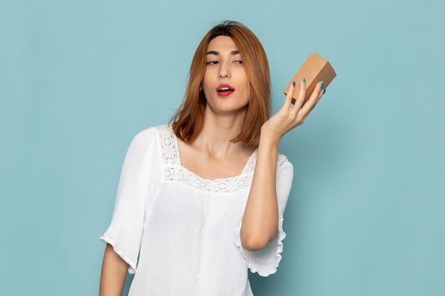 小さなギフトボックスを保持している白いドレスの女性