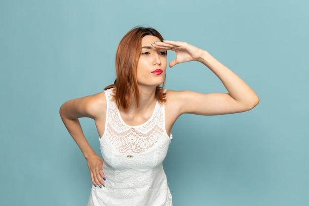 遠くを見ている白いドレスの女性