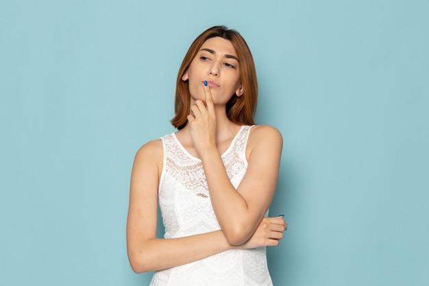 Женщина в белом платье позирует с выражением мышления