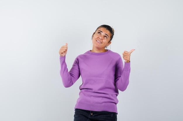 二重の親指を上げて幸せそうに見えるウールのブラウスの女性