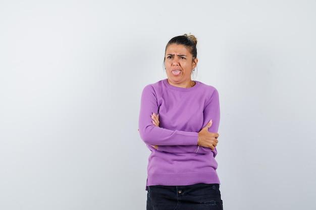 Девушка в шерстяной блузке стоит со скрещенными руками, высунув язык и задумчиво