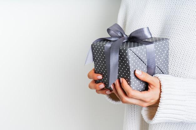 Девушки в шерстяной белый свитер, держа подарочной коробке с бантом. рождественский праздничный макет. макет на новый год.