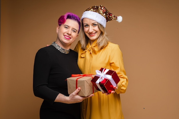 黄色いドレスを着た女性が彼女のガールフレンドの肩に腕を巻きつけ、笑顔でプレゼントを見せています。新年のコンセプト