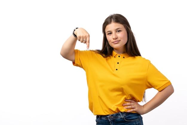 黄色のシャツとジーパンが白い背景の女性モデルの服で幸せな表情でポーズの女性