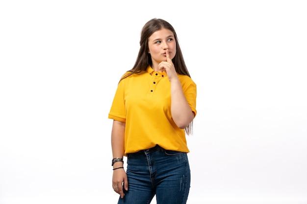 黄色のシャツとジーパンの白い背景の女性モデルの服の思考表現でポーズの女性