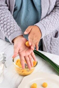 Женская индонезийская рука, округляющая биджи салак кабоча, торт из желтого сладкого картофеля или тыквенного риса, процесс приготовления на кухне приготовление такжила для бука пуаса рамадан завтрак
