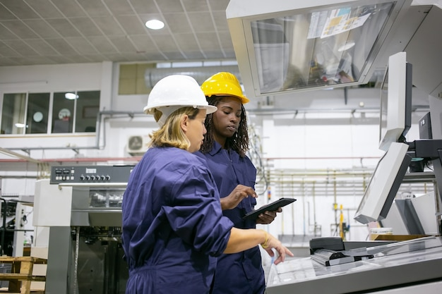 Female industrial employee teaching colleague to operate machine, pointing at control board, using tablet