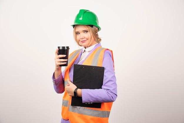 클립 보드와 흰 벽에 검은 컵 제복을 입은 여성 산업 엔지니어.
