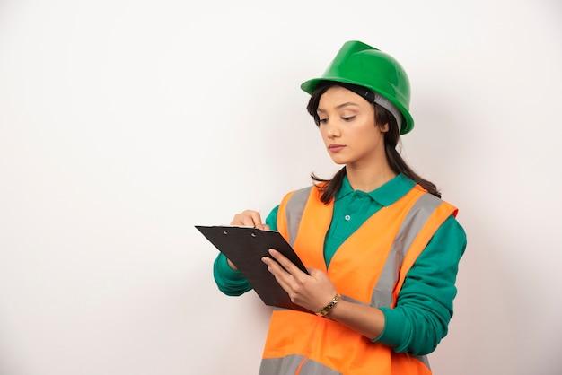 Ingegnere industriale femminile in uniforme con appunti su priorità bassa bianca.