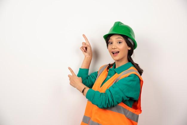 Ingegnere industriale femminile in uniforme con il casco su priorità bassa bianca. foto di alta qualità