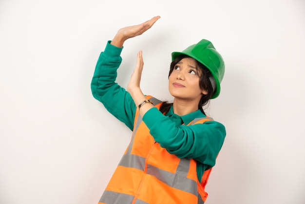 Ingegnere industriale femminile in uniforme con il casco su priorità bassa bianca.