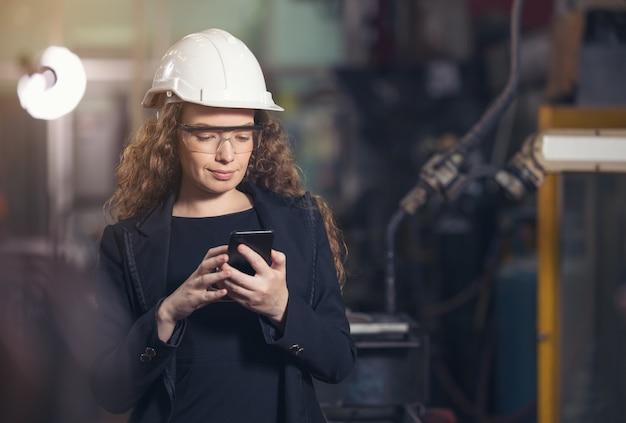 ヘルメットをかぶった女性の産業労働者は、工場で携帯電話を使用しています。