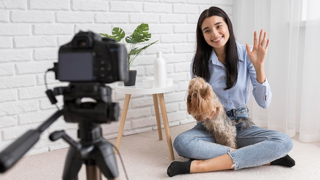 Женский влиятельный человек в домашнем видеоблоге с собакой