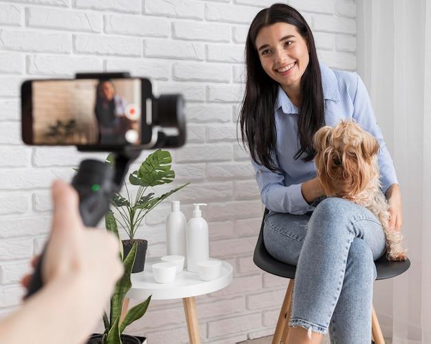 Женский влиятельный человек дома с собакой и смартфоном