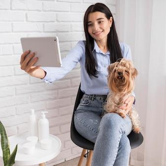 Женский влиятельный человек дома с собакой и планшетом