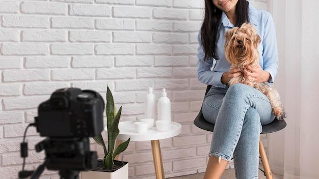 Женский влиятельный человек дома с собакой