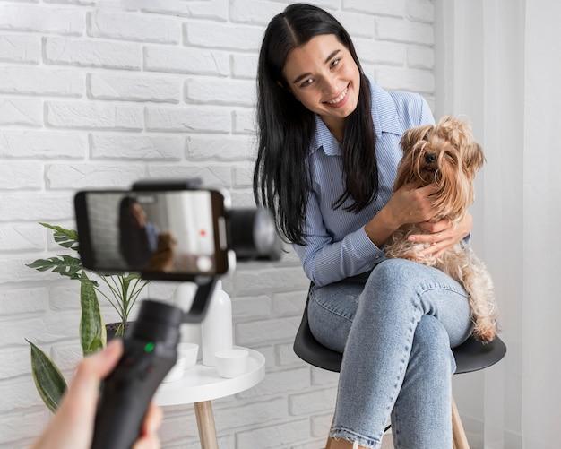 Женский влиятельный человек дома с домашним животным и смартфоном