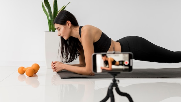 Female influencer at home vlogging while exercising with smartphone