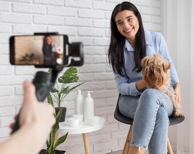 Female influencer at home with dog and smartphone