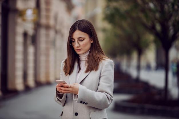 通りに立って、ソーシャルメディアに写真をアップロードするためにスマートフォンを使用している女性の影響力者。