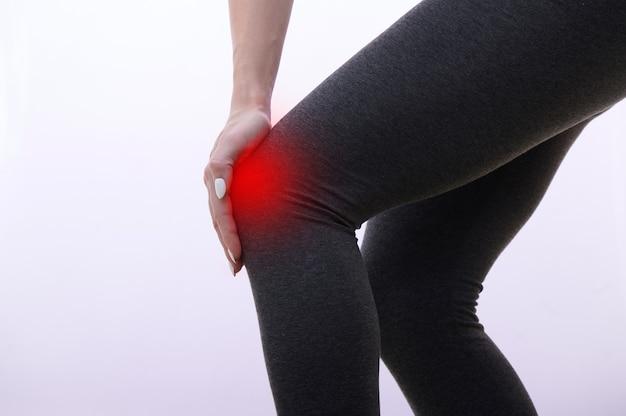 Женщина с травмой колена, больное место выделено красным маркером, женщина касается своей ноги руками.