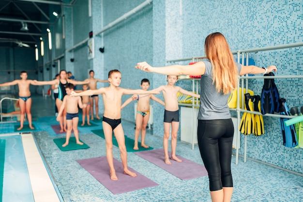 スイミングプールの近くでエクササイズをしている女性インストラクターと子供たちのグループ。健康で幸せな子供時代のコンセプト。現代のスポーツセンターでのスポーティーなキッズアクティビティ。